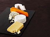 A selection of cheeses on a black platter