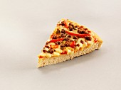 A slice of pizza with chilli peppers, beef and cheese