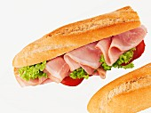 A ham baguette with lettuce and tomato