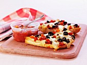 Two slices of pizza with olives and tomatoes