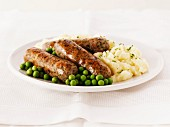 Pork and herb sausages with mashed potatoes and peas