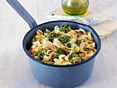 Tagliatelle with salmon, spinach and broccoli in a saucepan
