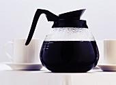 Kaffeekanne zwischen Kaffeetassen