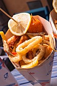 Fried fish and seafood with chips in a paper cone