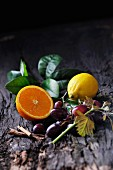 An arrangement featuring half and orange, a lemon, red grapes and cinnamon sticks on a piece of bark