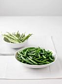 Frische grüne Bohnen und eine Schüssel gekochte grüne Bohnen