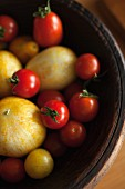 Red and yellow tomatoes with lemon cucumbers in a wooden bowl