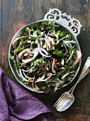 Kale salad with dried berries and almonds in a pewter bowl