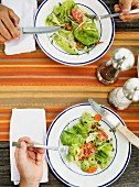 Two people eating salad (seen from above)