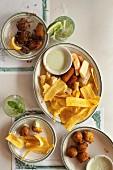 Teller mit frittierten, süssen Kochbananen, Dillmayonaise, Empanadas und gebratene Yuca-Sticks; dazu Schweinefleisch mit Reis und Bohnen, Fischkroketten und Mojitos