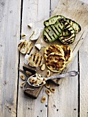 Grilled vegetables (avocado and garlic), almonds and lemons on a chopping board