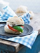 A bread roll with fresh cheese, tomato and basil leaves