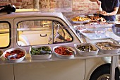 A buffet around a Fiat Cinquecento in the StraRipa aperitif bar, Naviglio Grande, Milan