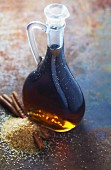 Cinnamon syrup in a bottle on a metal surface