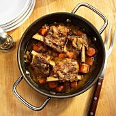 Beef ribs braised in beer with carrots, onions and celery in a pot
