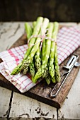 A bundle of green asparagus with a tea towel on a chopping board