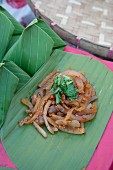 Spicy pork rind salad on a banana leaf (Thailand)