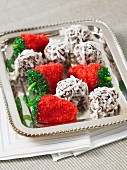 Chocolate and coconut balls and strawberry confectionery on a silver tray
