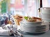 Tellerstapel, Besteck und Baguette mit Frischkäse