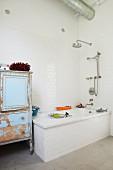 Badewanne und Vintage Schrank mit abblätternder Farbe in Bad mit weissen Wandfliesen
