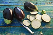 Whole aubergines and sliced aubergines on a rustic wooden table