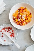 Persimon salad with pomegranate seeds and flaked almonds