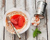 Tinned tomatoes on a plate with the empty tin next to it