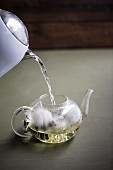 Hot water being poured into a teapot with tea bags
