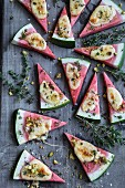 Gratinated watermelon slices with cheese, thyme and pistachios