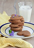 A stack of peanut butter and chocolate cookies shaped like hearts and stars with a glass of milk