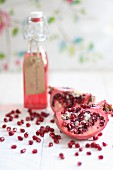 A bottle of pomegranate juice, sliced pomegranate and pomegranate seeds