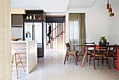 Essplatz mit Glasplatte und Holzstühlen neben der offenen Einbauküche mit zentraler Frühstückstheke, Treppe mit Abgrenzung durch raumhohe Holzstreben