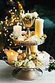 Brennende Kerzen und weisse Rosenblüten auf einer Etagere