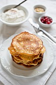 A stack of pancakes with coconut cinnamon quark, redcurrants and flaked almonds