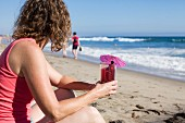 Woman sitting on beach holding glass of juice