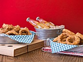 Fried onion rings in metal dishes with checked paper napkins