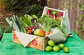 A wooden crate of fruit and vegetables on a rustic garden table