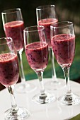 Blueberry and strawberry smoothies in stemmed glasses