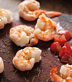 Fried shrimps, tomatoes and herbs on a wooden surface
