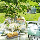 Table set for afternoon coffee with vase of spring flowers in garden