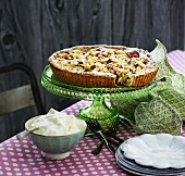 Rhubarb tart with almonds on a cake stand served with whipped cream