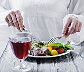 A glass of red wine in front of a plate of beff, tomato salad and dill potatoes