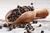 Black peppercorns in a wooden scoop