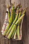 Green asparagus in a wire basket on a tea towel