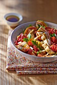 Pasta salad with colourful bow tie pasta, tomatoes and rocket