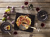 A puff pastry fig, smoked ham and feta cheese quiche on a baking tray, sliced