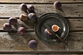 Fresh figs on a pewter plate and on a wooden table