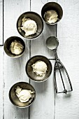 Mehrere Schalen Eiscreme mit weisser Schokolade und kandiertem Ingwer