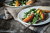 A green bean salad with grilled peaches and flaked almonds