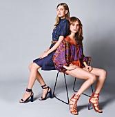 Zwei Frauen auf Stuhl mit Kleidung im Retro-Look